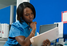 Female office worker doing paperwork. Physical and Cognitive Assessments for help in the work environment.