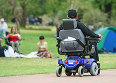 Male in powered wheelchair in park. Occupational Rehab Assessment to help with mobility.