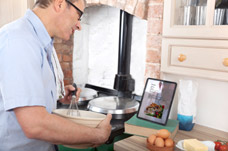Man using ipad to follow a recipe. Neuro rehabilitiation to help with cognitive functions.
